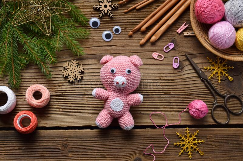 Pink pig, symbol of 2019. Happy New Year. Crochet toy for child. On table threads, needles, hook, cotton yarn. Handmade crafts on. Holiday with your own hands stock images
