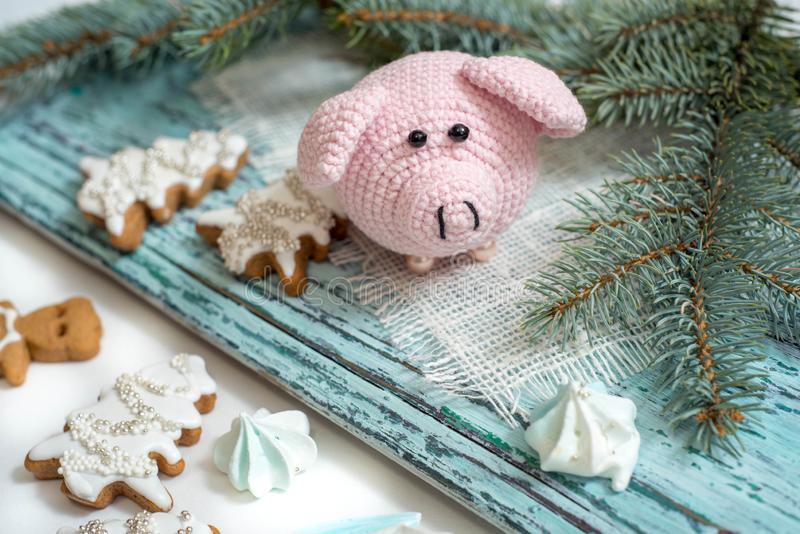 Pink pig, symbol of 2019. Happy New Year. Crochet toy for child. On table threads, needles, hook, cotton yarn. Handmade crafts on royalty free stock images