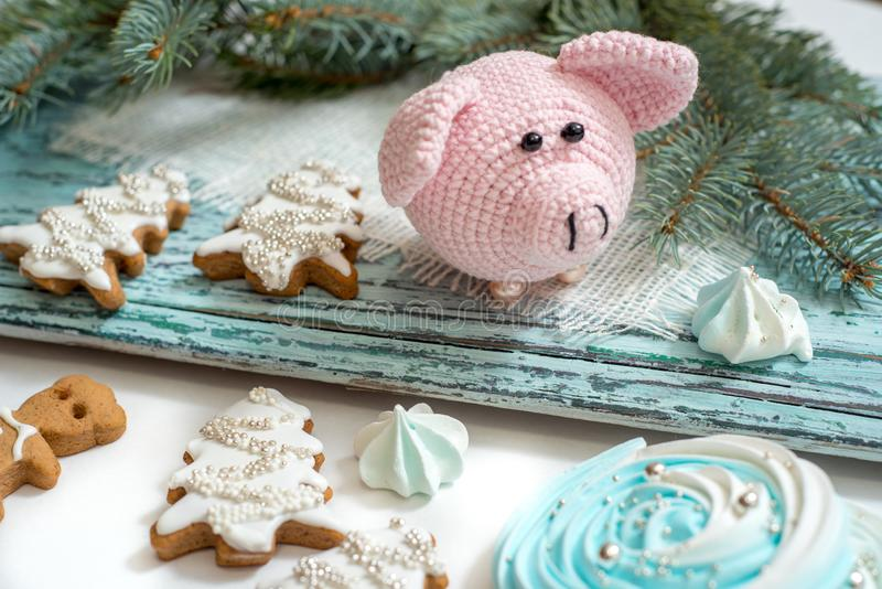 Pink pig, symbol of 2019. Happy New Year. Crochet toy for child. On table threads, needles, hook, cotton yarn. Handmade crafts on royalty free stock photo