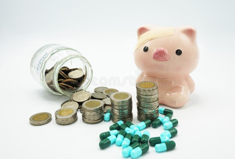 A pink piggy bank with a bandage at head behind stacking coins and blue green capsules pillon white background ,. Conceptual for increasing medical expense for stock photography