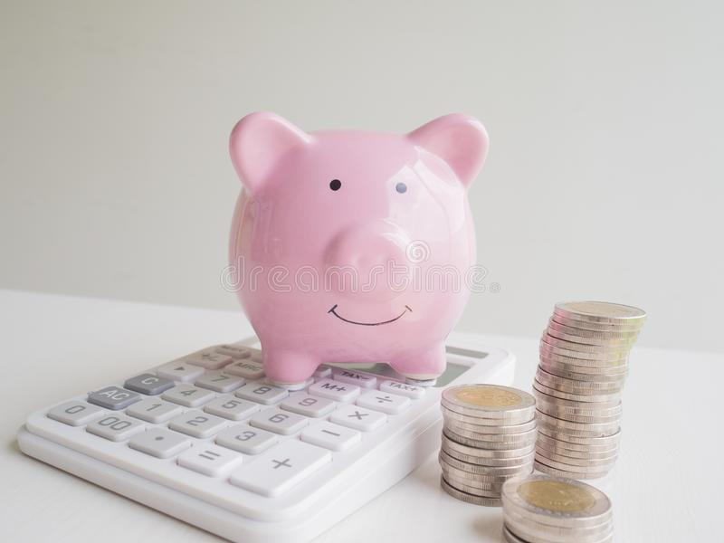 Pink Piggy bank and calculator  with coins pile, Saving money for future plan and retirement fund concept.  royalty free stock photos