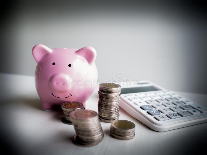 Pink Piggy bank and calculator  with coins pile, Saving money for future plan and retirement fund concept.  stock images