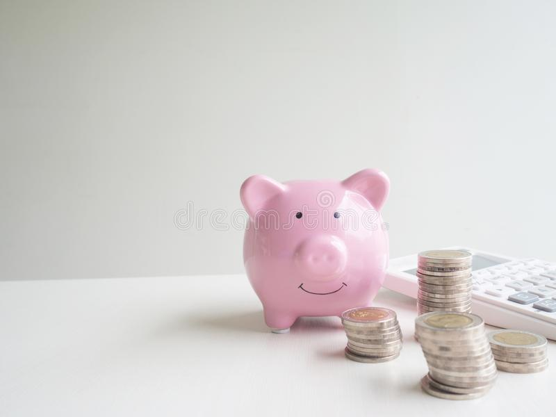 Pink Piggy bank and calculator  with coins pile, Saving money for future plan and retirement fund concept.  stock photos