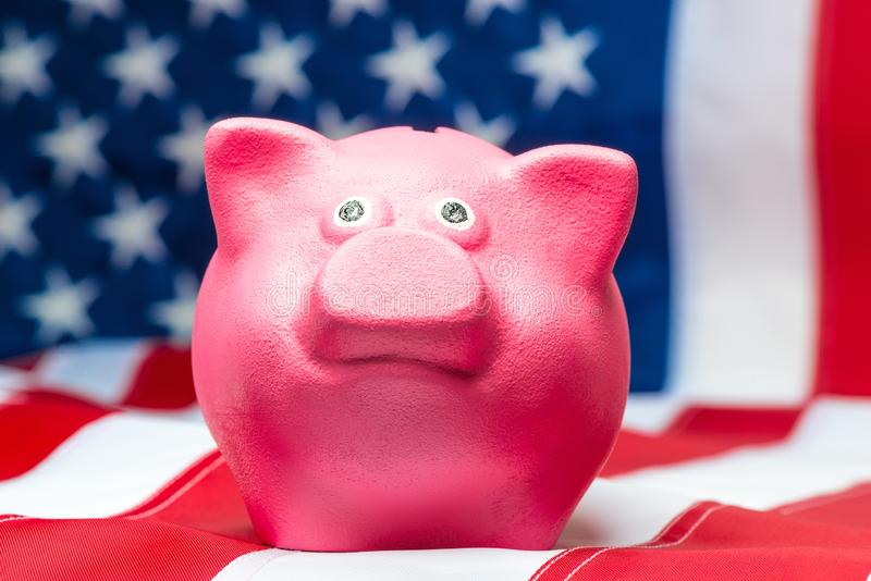 Pink piggy bank close up. On American flag royalty free stock image