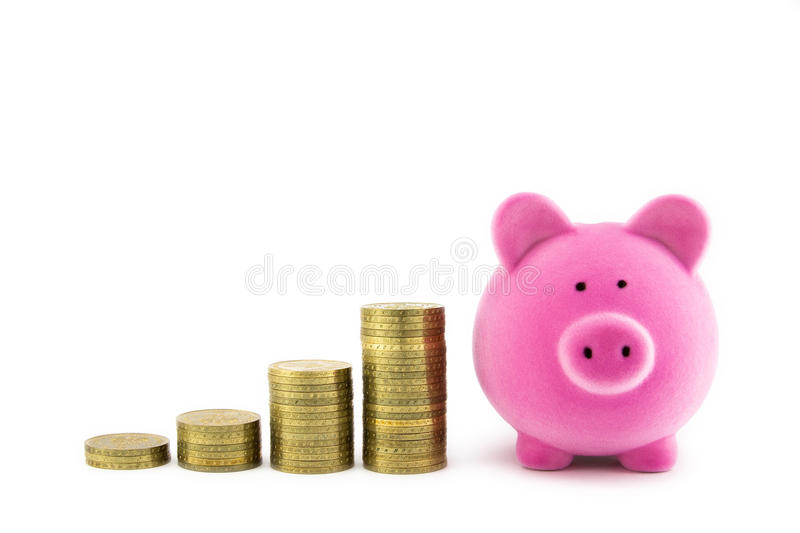 Pink piggy bank and coins stock image