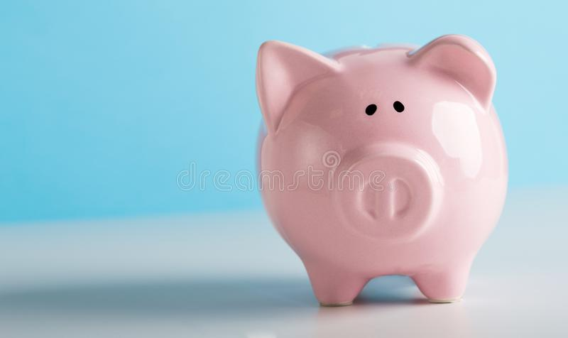 Pink piggy bank for coins savings on blue background. Financial concept. Pink piggy bank for coins savings on blue background, panorama, copy space stock image