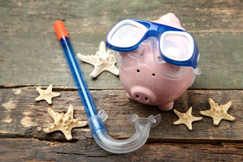 Piggy bank with diving mask and snorkel. Pink piggy bank with diving mask and snorkel on wooden table stock photography