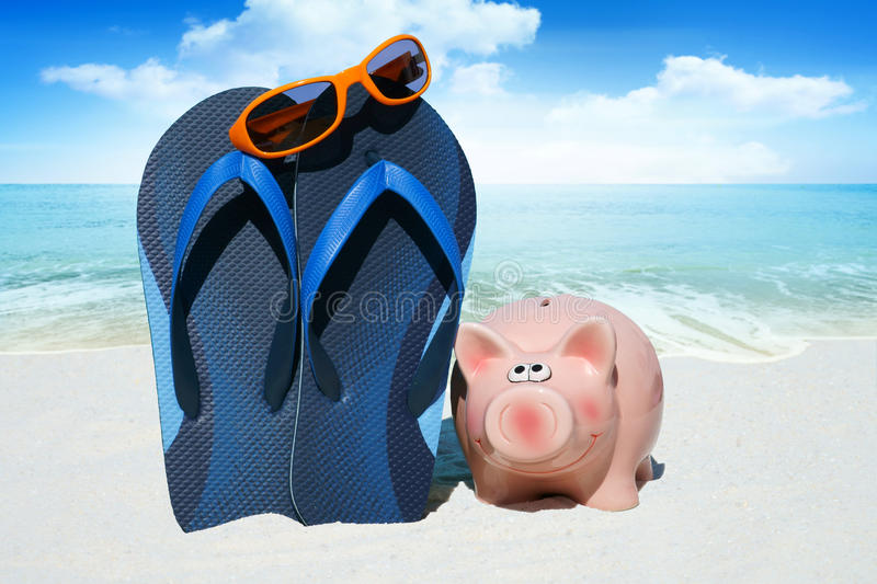 Pink piggy bank and Flip Flops. Pink piggy bank, Sunglasses and blue Flip Flops on the Beach stock photo