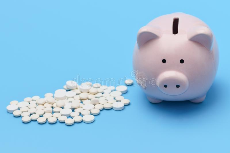 Pink piggy Bank in the form of a pig is on the right blue background, on the left are round  pills royalty free stock photo
