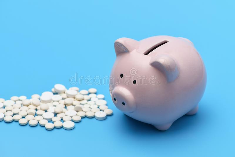 Pink piggy Bank in the form of a pig is on the right blue background, on the left are round white pills stock photos