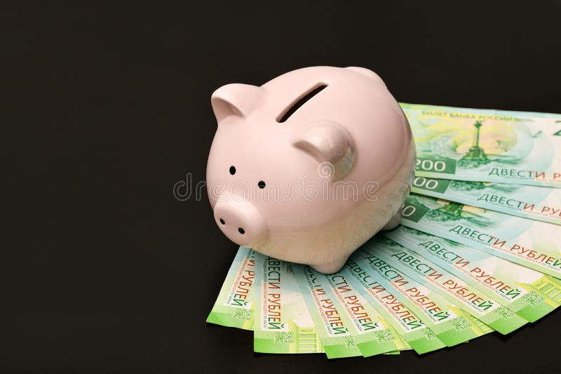 Pink piggy Bank in the form of a pig is worth on Russian money d royalty free stock image