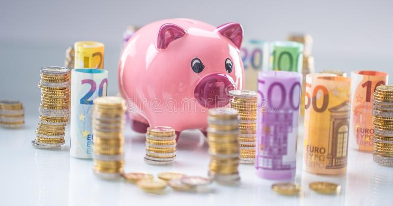 Pink piggy bank in the middle of rolled euro banknotes and towers with coins stock photo