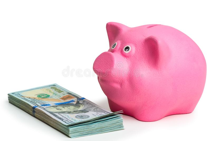 Pink piggy bank and pile of american dollars on white background isolated. Side view royalty free stock photography