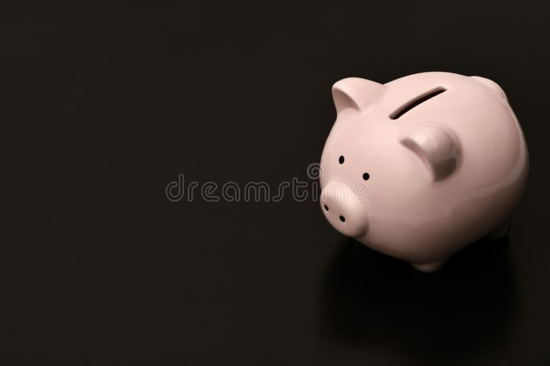 Pink piggy Bank is on the right on a black background, on the l royalty free stock images