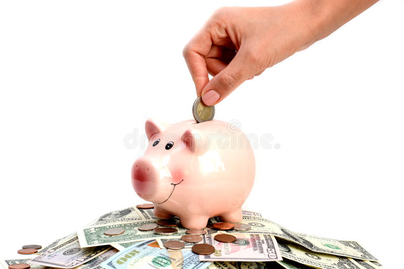 Pink piggy bank standing on a pile of coins and bills, suggesting money savings concept royalty free stock images