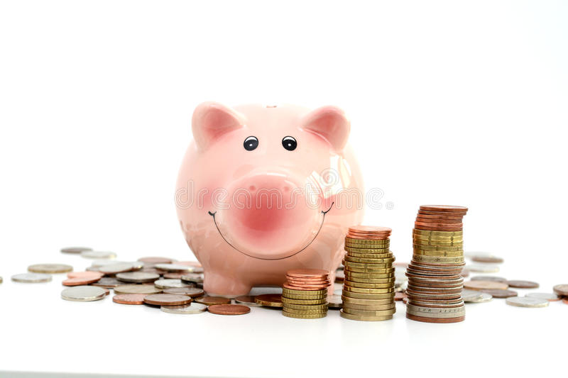 Pink piggy bank standing on a pile of coins, suggesting money savings concept stock image