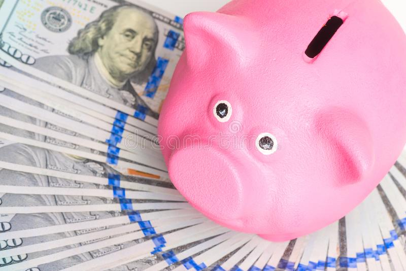 Pink piggy bank stands on a fan of a pile of american dollars on a white background. Top view stock images