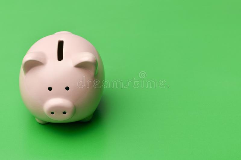 Pink piggy Bank stands on the left on a green background. On the stock image
