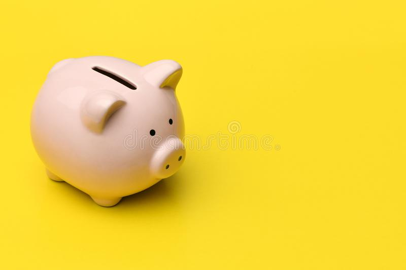 Pink piggy Bank stands on the left on a yellow background. On th stock photography