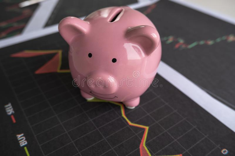 Pink piggy bank with stock graph, step up growing business to success and saving for retirement concept.  royalty free stock photography