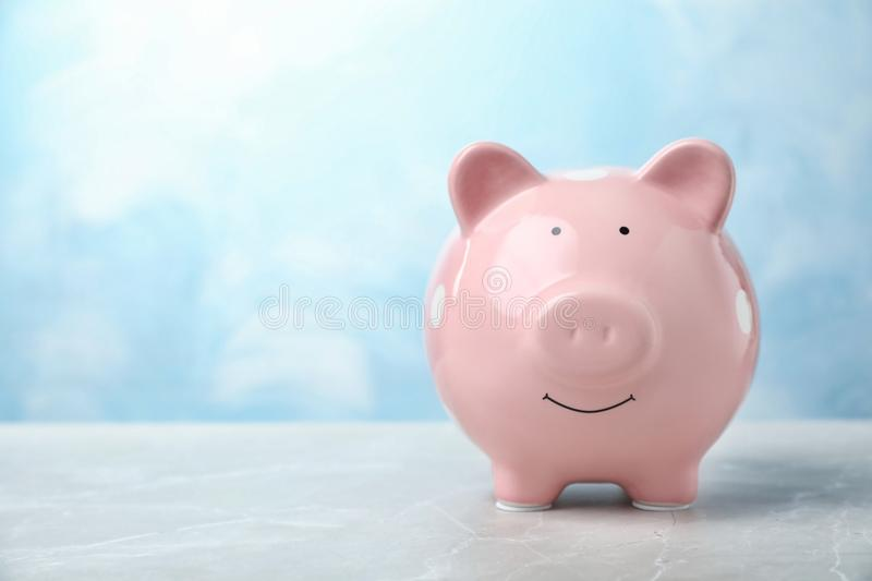 Pink piggy bank on table. Money saving royalty free stock image