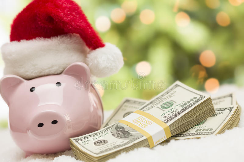 Pink Piggy Bank Wearing Santa Hat Near Stacks of Money on Snowflakes royalty free stock images
