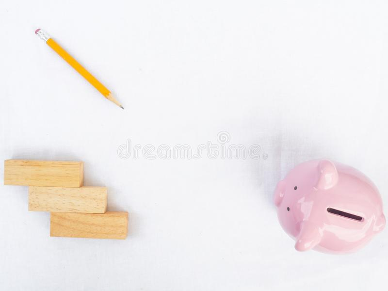 Pink piggy bank on white background with wooden block and yellow pencil, Drawing own way to saving money for future plan royalty free stock image