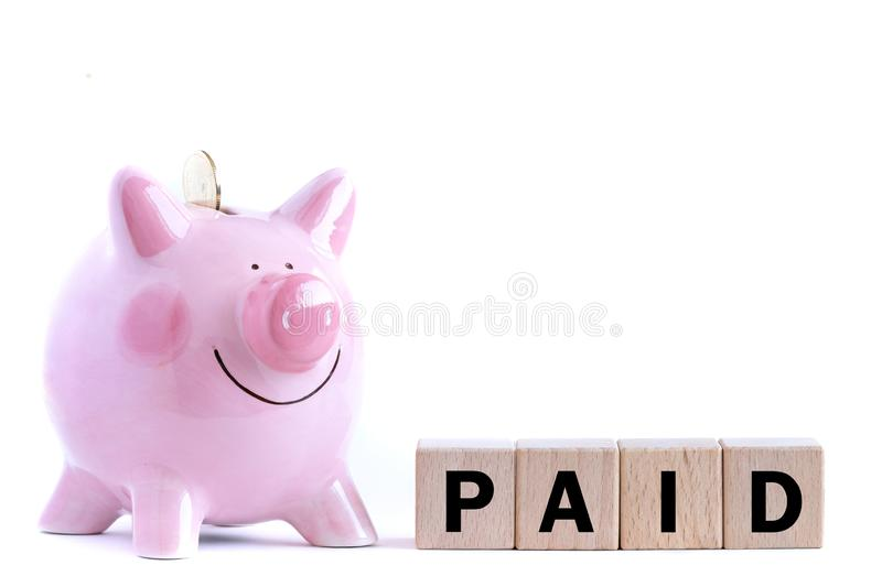 Pink piggy bank and wooden blocks with text. A pink piggy bank and wooden blocks with text.   Isolated on white background home concept money paid sale buying royalty free stock photos
