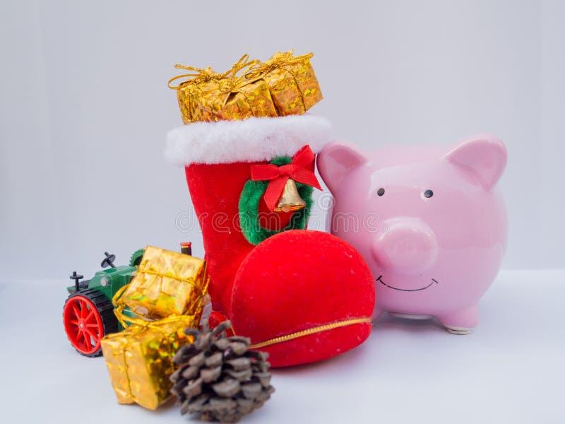 Pink Piggy Bank y Santa boot con decoración de fondo blanco, tengan unas buenas vacaciones en esta Navidad fotografía de archivo