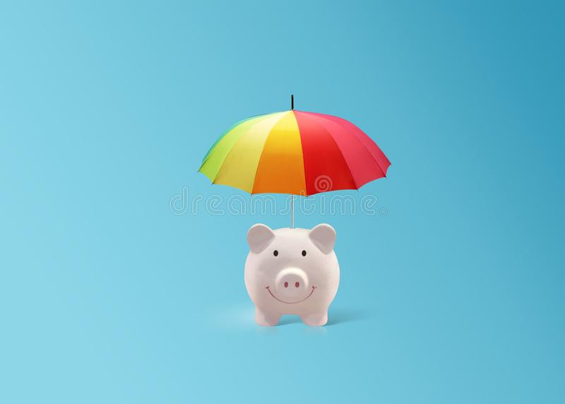 Pink piggy ceramic bank with colorful rainbow umbrella, insurance royalty free stock photos