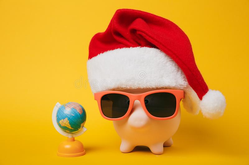 Pink piggy money bank with sunglasses Christmas hat, toy Earth world globe on yellow background. Money. Accumulation investment banking services wealth concept stock photo