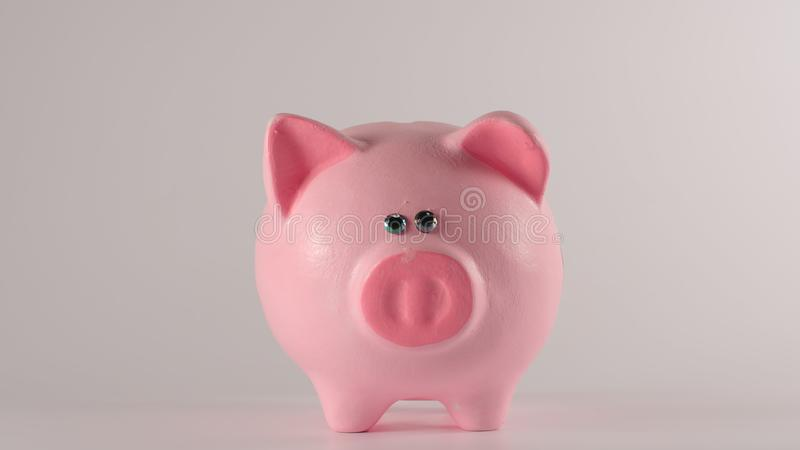 Pink piggy moneybox on a white background - Front view stock photo
