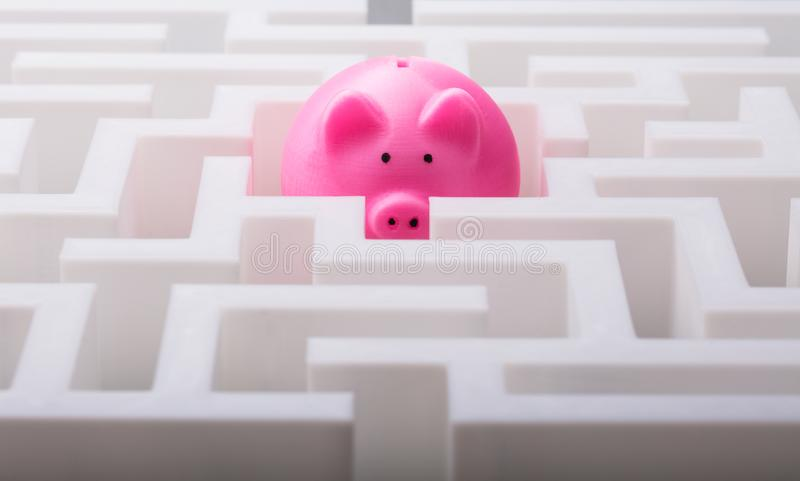Pink Piggybank In The Centre Of Maze. Close-up Of Pink Piggybank In The Centre Of White Maze royalty free stock photo