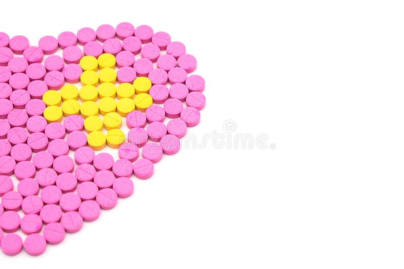 Pink pill is heart shaped and Yellow pills are placed in a cross shape. Creative healthcare and medicine concept stock photo