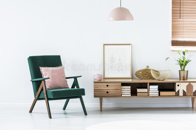 Pink and green living room. Pink pillow on green armchair next to a rustic cupboard in living room interior with poster stock image