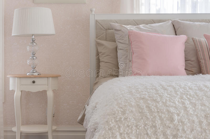 Pink pillow on white luxury bed in bedroom stock photography