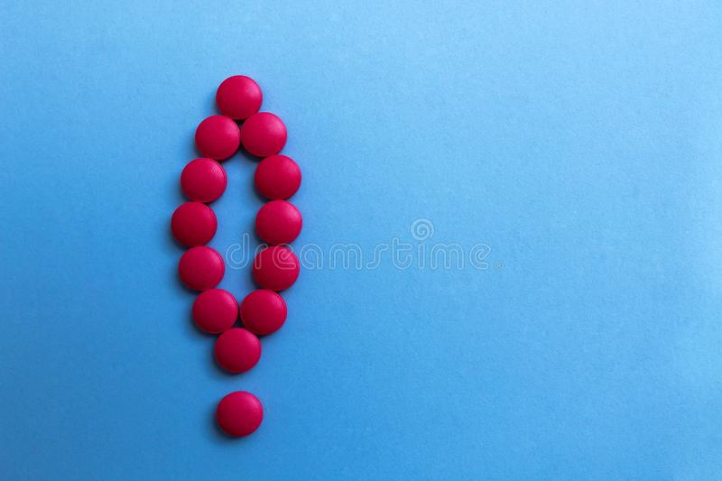 Pink pills lined up with an exclamation mark. Exclamation, mark, pills, health, blue, background, care, medicine, illness, pharmacy, medical, pill, drug royalty free stock photo