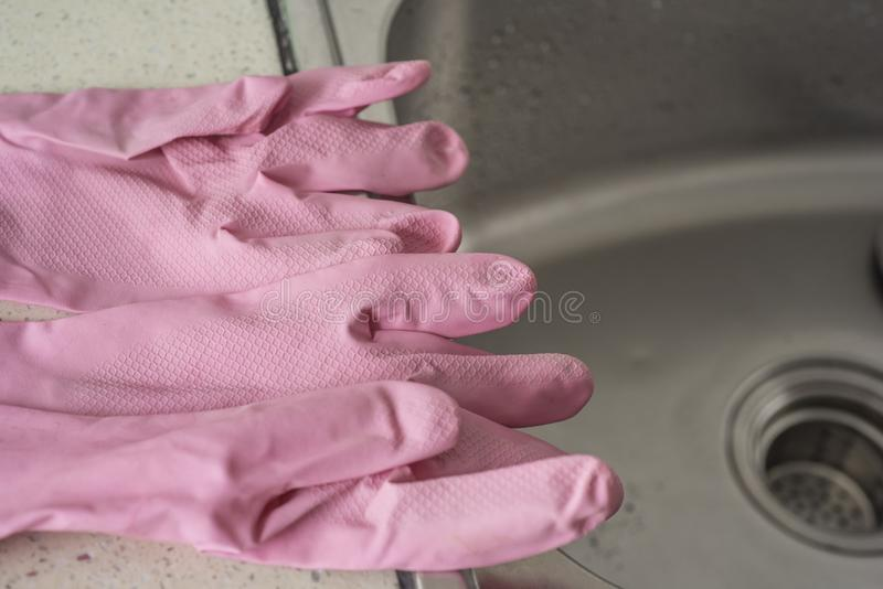 Pink plastic gloves on a stainless steel sink. Daily necessities, kitchen scene, pink plastic gloves on a stainless steel sink royalty free stock photo