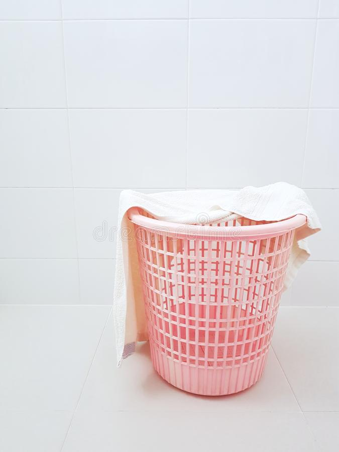 Pink plastic laundry basket and dirty towel in the laundry room stock photo