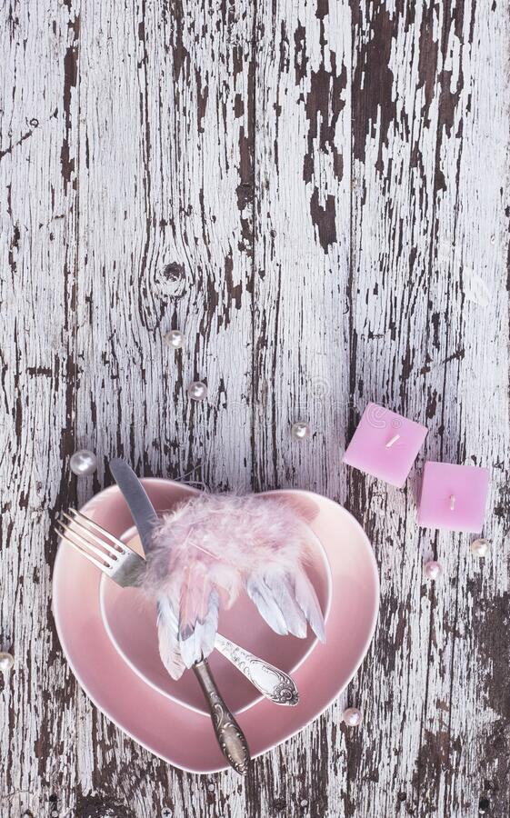 Pink plate in the shape of a heart with silver knife and fork, candles and decorative wings on white wooden background. Top view. stock image