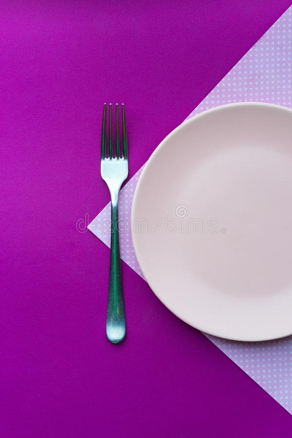 Pink plate on a pink tablecloth stock image