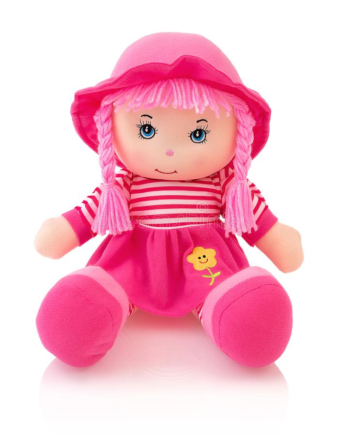 Pink plushie doll isolated on white background with shadow reflection. Cute pinky rag baby doll sitting on white underlay. Nice contemporary rag baby with pink stock images