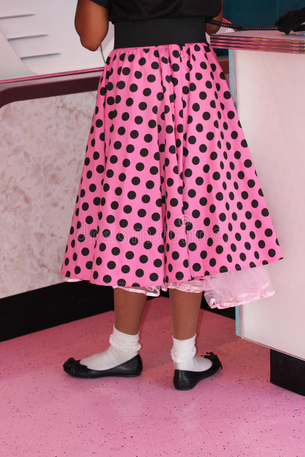 Pink polka dotted poodle skirt stock photography