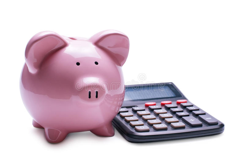 Pink porcelain piggy bank near a desk calculator royalty free stock photo