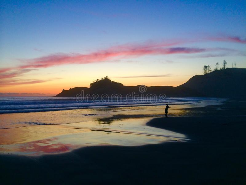 Small silhouetted boy playing in pacific ocean tide, reflecting blue,pink, orange sunset sky royalty free stock photography