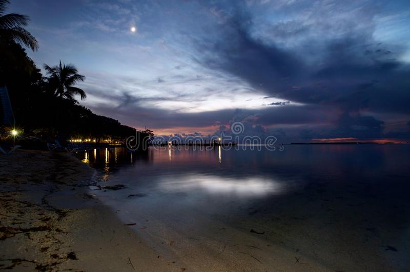 Pink and purple clouds after sunset with moon and dock stock photography