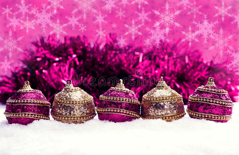 Pink and purple and gold Christmas balls in snow with tinsel and snowflakes, christmas background royalty free stock image