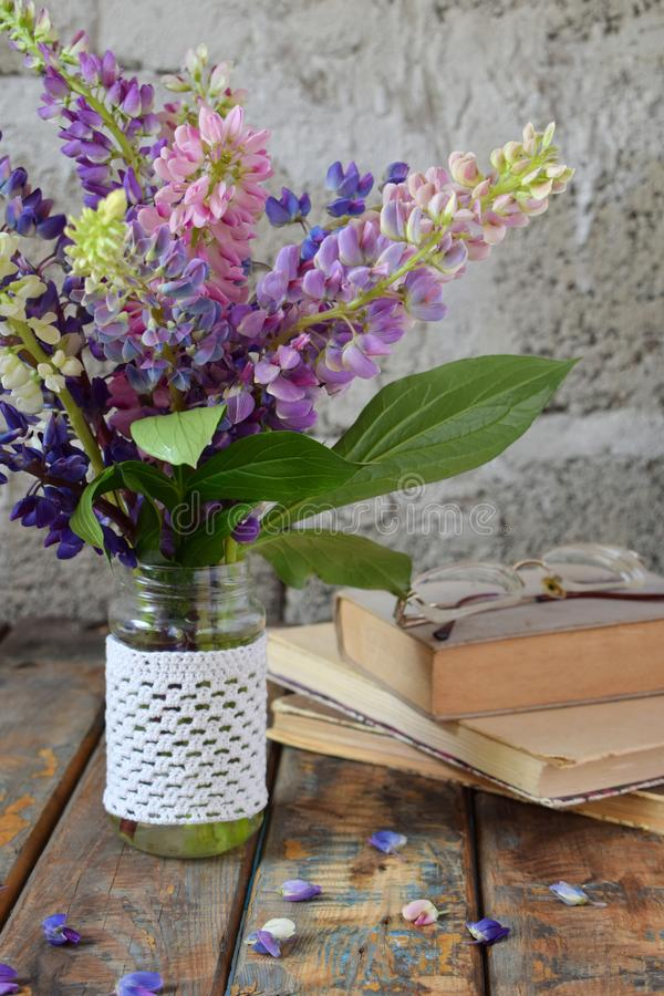Pink, purple lupine flowers bouquet in vase and old book. Birthday, Mother`s day, Valentine`s Day, March 8, Wedding card or stock image