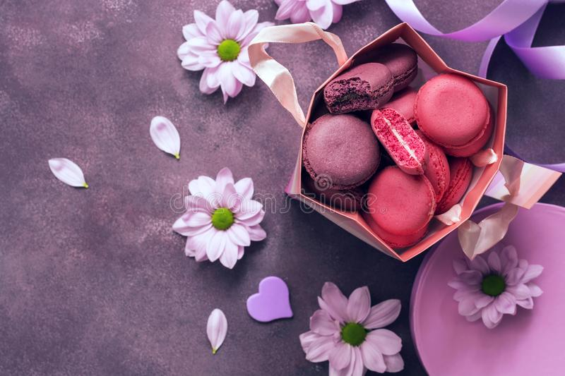 Pink and purple macaroon close-up in a gift paper bag on a purple background decorated with flowers. Top view, selective focus. royalty free stock image