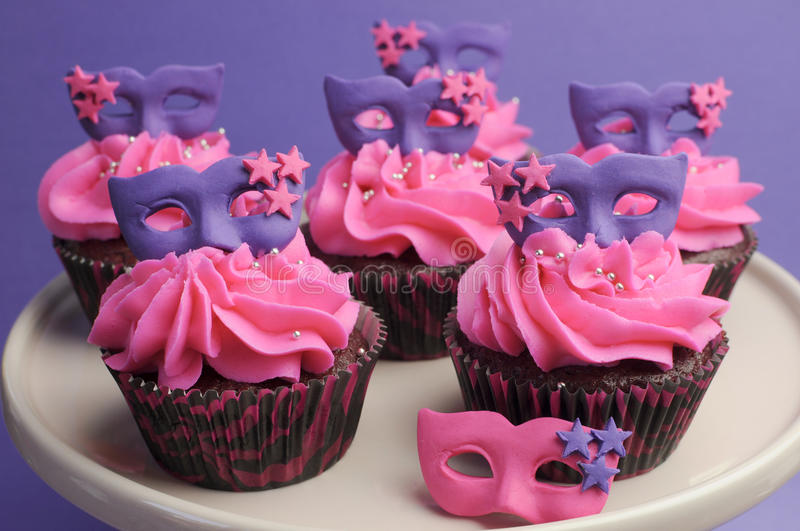 Pink and purple masquerade masks decorated party c. Upcakes with pink frosting for teenage, birthday, New Years Eve, or wedding bridal shower party - close up stock photography